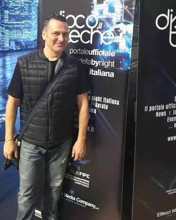 Nella foto, Andrea Belli posa davanti allo stand di discoteche.it